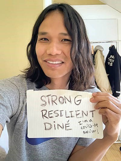 "Alastair displays handwritten sign that reads ""Strong Resilient Dine"""